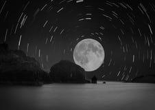 Mond- und Sternspuren über dem Meer Stockfotografie