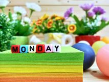Monday. Colorful cube letters on sticky note block. Monday. Colorful cube letters on sticky note block and wooden pallets as a background royalty free stock photo