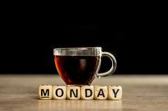 It is monday concept. Glass cup of coffee sitting on wooden letter blocks that assemble the word Monday stock image