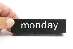 Monday. Hand holding a black wooden block with the word monday written on it stock photography