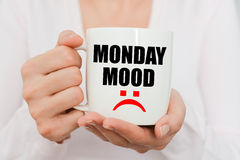 Monday mood with sad symbol on white coffee cup. Held by a woman Stock Images