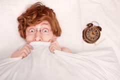 Monday morning. Funny guy in bed, alarm clock Royalty Free Stock Images