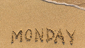 Monday - word drawn on the sand beach. With the soft wave royalty free stock photography