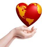 Monde de coeur dans des mains Image stock