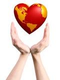 Monde de coeur dans des mains Photographie stock