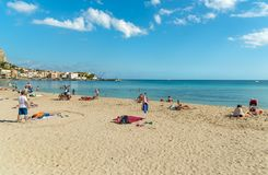 People enjoying beach of Mondello on an autumn day, is a small seaside resort near center of city Palermo. stock photos