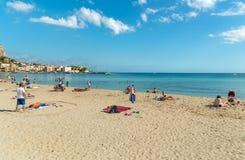People enjoying beach of Mondello on an autumn day, is a small seaside resort near center of city Palermo. Stock Photos
