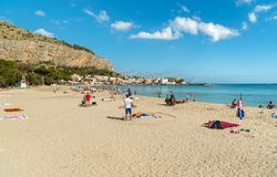 People enjoying beach of Mondello on an autumn day, is a small seaside resort near center of city Palermo. stock photography