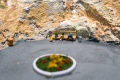 Mondo miniatura: la gente che aspetta il loro trasporto sulla fermata dell'autobus Tema di trasporto pubblico e di turismo Immagini Stock
