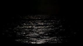 Mondscheinweg mit niedrigem Dummkopfmond ?ber dem Meer stock footage