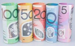 Moneda australiana de los billetes de banco rodada encima de denominaciones Foto de archivo
