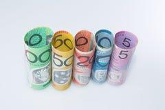 Moneda australiana de los billetes de banco rodada encima de denominaciones Foto de archivo libre de regalías