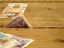 Moneda británica exprimida entre las líneas imagen de archivo