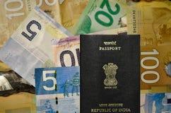 Moneda canadiense de la denominación 5, 10, 20, 100 con el pasaporte indio Foto de archivo libre de regalías