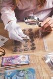 Moneda cobrable en la mano del ` s de la mujer a través de la lupa fotos de archivo libres de regalías
