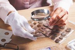 Moneda cobrable en la mano del ` s de la mujer a través de la lupa imagenes de archivo