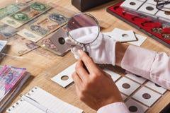 Moneda cobrable vieja en la mano del ` s de la mujer foto de archivo