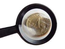 Moneda 1 dólar debajo de una lupa Fotos de archivo