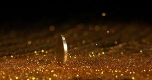 Moneda de 1 balanceo del euro en polvo del oro contra el fondo negro, cámara lenta almacen de video