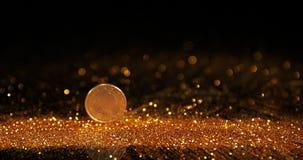 Moneda de 1 balanceo del euro en polvo del oro contra el fondo negro, cámara lenta almacen de metraje de vídeo