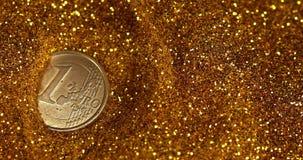 Moneda de 1 balanceo del euro en polvo del oro contra el fondo negro, cámara lenta metrajes