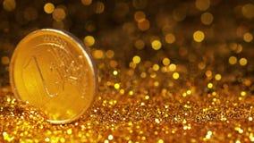 Moneda de 1 balanceo del euro en polvo del oro contra fondo negro, almacen de metraje de vídeo