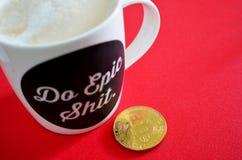 Moneda de Bitcoin con lema de la epopeya de la taza de café fotos de archivo