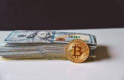 Moneda de Bitcoin contra la pila de dinero, 100 cientos billetes de dólar Foto de archivo libre de regalías