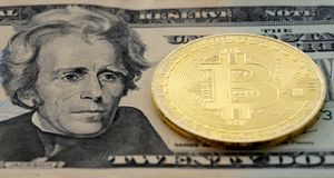 Moneda de Bitcoin en el billete de dólar $20 de Estados Unidos los E.E.U.U. veinte Imagenes de archivo