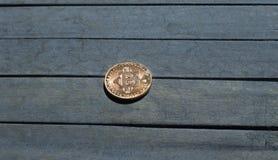 Moneda de Bitcoin en el escritorio de madera Imagen de archivo libre de regalías