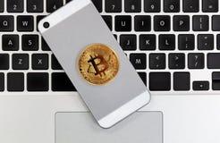 Moneda de Bitcoin en el teléfono elegante con el teclado de ordenador en backgr Imagen de archivo