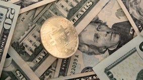 Moneda de Bitcoin en la cámara lenta de los billetes de dólar $20 de Estados Unidos los E.E.U.U. veinte que gira metrajes