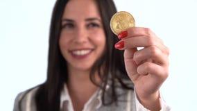Moneda de Bitcoin en la mano de la mujer metrajes