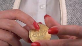 Moneda de Bitcoin en la mano de la mujer almacen de metraje de vídeo
