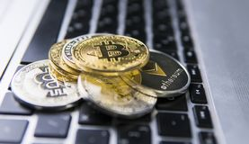 Moneda de Bitcoin en un top de otras monedas crypto en un teclado del ordenador portátil Monedas de oro de Bitcoin Inversión de C fotos de archivo libres de regalías