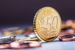 Moneda de cincuenta centavos en el borde Dinero euro Dinero en circulación euro Monedas euro apiladas en uno a en diversas posici Fotografía de archivo libre de regalías