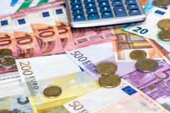 Moneda de la calculadora y del euro que miente en euro Imagen de archivo libre de regalías