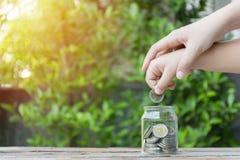 Moneda de la niña y de la pila para ahorrar Concepto del ahorro del dinero imágenes de archivo libres de regalías