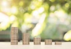 Moneda de la pila con el fondo verde de la luz del bokeh ahorre el dinero creciente Fotografía de archivo libre de regalías