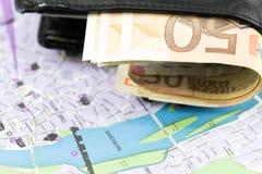 Moneda de la unión europea en una cartera y un mapa Fotografía de archivo