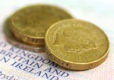 Moneda de libra británica en un pasaporte Foto de archivo