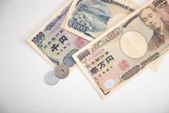 Moneda de los billetes de banco de los yenes japoneses y de los yenes japoneses Imágenes de archivo libres de regalías