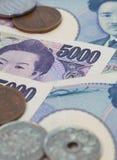 Moneda de los billetes de banco de los yenes japoneses y de los yenes japoneses Foto de archivo libre de regalías