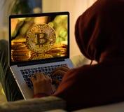 Moneda de oro de Bitcoin y sittign anónimo del pirata informático con el ordenador portátil imagenes de archivo
