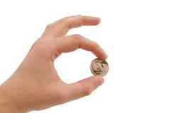Moneda de oro de la explotación agrícola de la mano entre los dedos Fotografía de archivo