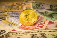 Moneda de oro del bitcoin sobre cuentas del dólar, del euro y del yuan imágenes de archivo libres de regalías
