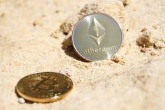 Moneda de oro del ethereum y del bitcoin en fondo arenoso Foto de archivo