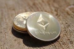 Moneda de oro del ethereum y del bitcoin en fondo de madera Foto de archivo libre de regalías
