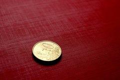 Moneda de oro en superficie roja Fotos de archivo