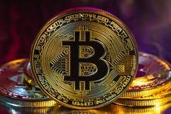 Moneda de oro física del bitcoin de Cryptocurrency en fondo colorido Imagen de archivo